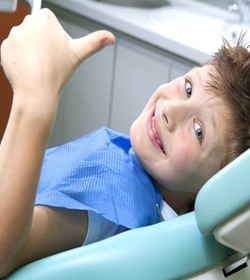 Boy smiling with thumb's up in dental chair